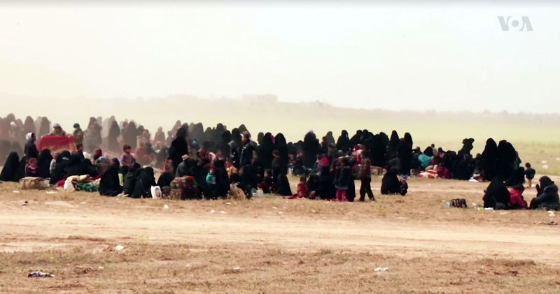 Des familles de combattants de l'État Islamique (Daech) faits prisonniers par les Forces Démocratiques Syriennes en Syrie de l'est (8 mars 2019). Source : https://www.voanews.com/a/more-is-wives-flee-syria-s-baghuz/4821141.html ; Wikimedia commons)